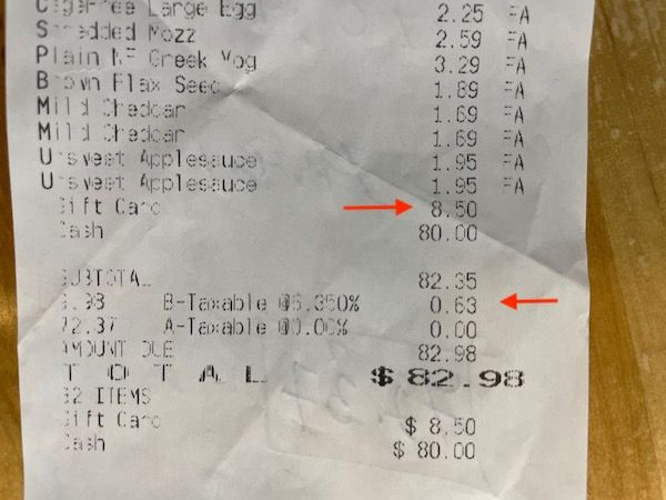 Aldi grocery receipt with the tax and gift card highlighted with an arrow.